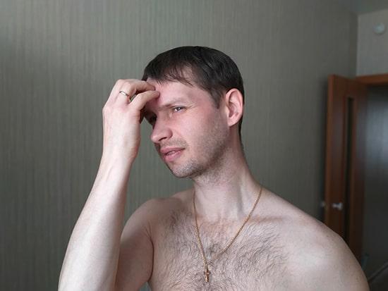 мужчина чешет лоб