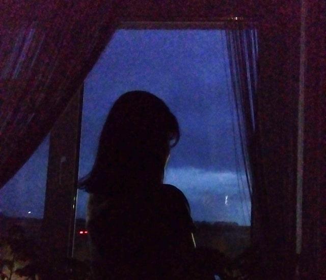 смотрит в окно ночью